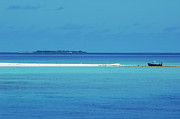 Locations Metal Prints - Fishing boat anchored on a white sand beach with a tropical island in the background in Maldives Metal Print by Sami Sarkis