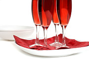 Sparkling Wine Posters - Four glasses of rose champagne on a red napkin isolated on white Poster by David Smith