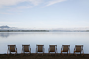 Outdoor Chair Posters - Germany, Bavaria, Chiemsee, Row Of Folded Chairs By Lake Poster by Westend61