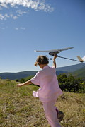 Enjoyment Photos - Girl flying model plane in field by Sami Sarkis