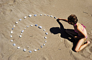 Enjoyment Photos - Girl on beach displaying pebbles in spiral shape by Sami Sarkis