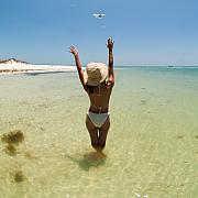Beach Posters - Girl on Beach waving to Airplane Poster by Rolf Bertram