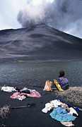 Routine Posters - Girl washing clothes in a lake with the Mount Yasur volcano emitting smoke in the background Poster by Sami Sarkis