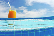 Juice Posters - Glass of orange juice on pool ledge Poster by Sami Sarkis