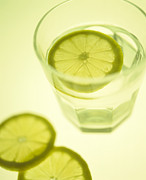 Sliced Prints - Glass Of Water With Sliced Lemon Print by Lawrence Lawry
