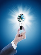 Creativity Metal Prints - Hand holding light bulb with globe  Metal Print by Setsiri Silapasuwanchai