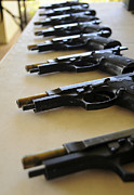 Revolvers Photos - Handguns Lined Up On A Table by Stocktrek Images