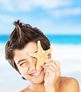 Preteen Framed Prints - Happy face boy with starfish on the beach Framed Print by Anna Omelchenko