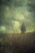 Atmosphere Posters - Hooded man walking in field with storm clouds Poster by Sandra Cunningham