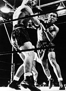 Boxing Photo Framed Prints - Joe Louis Delivers Knockout Punch Framed Print by Everett