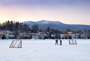 Kids Playing Hockey Photos - Kids playing hockey on Mirror Lake with Lake Placid Village shown in the background at sunset  by Brendan Reals