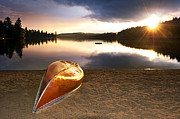 Fall Trees Posters - Lake sunset with canoe on beach Poster by Elena Elisseeva