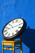Clock Photo Framed Prints - Large clock on yellow chair Framed Print by Garry Gay