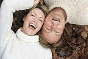 Women Together Prints - Laughing Couple Lying On Autumn Leaves Print by Ian Boddy