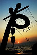 Locations Framed Prints - Lifebuoy silhouetted on a fishing boat at sunset Framed Print by Sami Sarkis