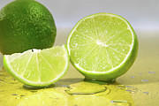 Thirst Posters - Limes on yellow surface Poster by Sandra Cunningham