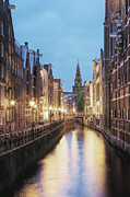 Reflective Art - Lit Canal Between Buildings by Andersen Ross