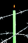 Barbed Wire Fences Photo Prints - Lit candle surrounded by barbed wire Print by Sami Sarkis