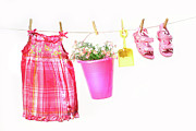Bright Colored Prints - Little girl clothes and toys on a clothesline Print by Sandra Cunningham