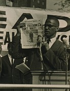 Malcolm X Prints - Malcolm X, Holding Up Newspaper Print by Everett