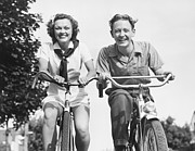 Young Adult Framed Prints - Man And Woman Riding Bikes, (b&w), Low Angle View Framed Print by George Marks