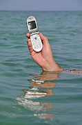 On The Phone Prints - Man hand holding cellphone out of sea surface Print by Sami Sarkis