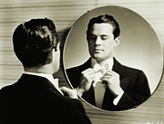 Evening Wear Framed Prints - Man In Tuxedo Adjusting His Bowtie (1940) Framed Print by Archive Holdings Inc.