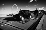 London Cab Posters - Man On Hired Cycle Being Overtaken By Black London Cab Taxi On Westminster Bridge Poster by Joe Fox