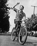 18-19 Years Prints - Man Riding Bicycle, Waving, (b&w) Print by George Marks