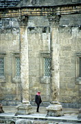 Roman Ruins Posters - Man walking between columns at the Roman Theatre Poster by Sami Sarkis