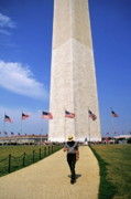 Star Spangled Banner Photos - Man walking down a footpath with the Washington Monument in the background by Sami Sarkis