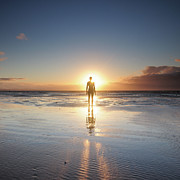 Sunset Reflection Prints - Man Walking On Beach At Sunset Print by Stu Meech