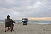 Arts Edge Posters - Man watching TV on beach at sunset Poster by Sami Sarkis