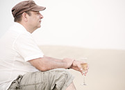 Prosecco Prints - Man with glass of champagner in the dunes Print by Iryna Shpulak