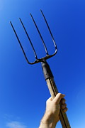 Pitchfork Prints - Mans hand holding up pitchfork against blue sky Print by Sami Sarkis