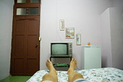 Hotel-room Photo Prints - Mans legs on a bed in front of an old TV Print by Sami Sarkis