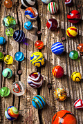 Plaything Prints - Marbles on wooden board Print by Garry Gay