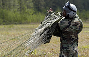 Camouflage Photos - Marine Rolls Up His Parachute by Stocktrek Images