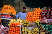 Food Vendors Framed Prints - Market vendor selling fruit in a bazaar Framed Print by Sami Sarkis