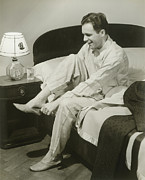 Pajamas Prints - Mature Man Sitting On Bed Putting On Slippers, Smiling Print by George Marks