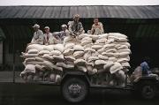Harsh Conditions Art - Men Sit On Bags Of Flour by Justin Guariglia