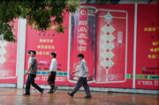 Footpaths Art - Men walking past a huge advertisement while walking down the street together in Beijing by Sami Sarkis