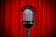 Interview Prints - Microphone on stage with spotlight on red curtain Print by Richard Thomas