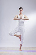 One Woman Only Prints - Mid Adult Woman In Tree Pose Against White Background Print by Westend61
