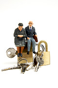 Couples Photo Prints - Miniature figurines of elderly couple sitting on padlocks Print by Bernard Jaubert