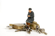Miniatures Prints - Miniature figurines of elderly sitting on padlocks Print by Bernard Jaubert