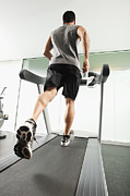 Treadmill Prints - Mixed Race Man Running On Treadmill Print by Erik Isakson