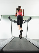 Woman Of Color Posters - Mixed Race Woman Running On Treadmill Poster by Erik Isakson