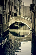 Mirroring Prints - narrow channel with a bridge in Venice Print by Joana Kruse
