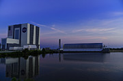 Ksc: K.s.c. Art - NASA VAB and Pegasus barge at sunrise with reflections in water  by Chris Haber